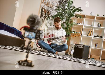 Kraft der Musik. In der Nähe des digitalen Kamera Bildschirm mit männlichen Musik blogger spielen, E-Gitarre und Aufnahme von neuen Video für seine vlog - Stockfoto