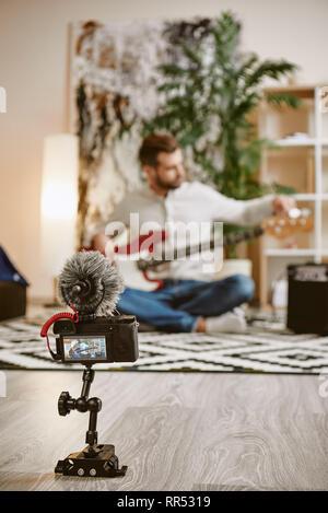 Einstellen einer Sound. In der Nähe des digitalen Kamera Bildschirm mit männlichen Musik blogger einstellen E-Gitarre und Aufnahme von neuen Video für Vlog. Youtube kan. - Stockfoto