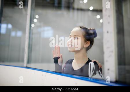 Portrait von hoffnungsvollen Mädchen beobachten Eiskunstlauf Ausbildung durch Glas und verträumt lächelnd, Kopie Raum - Stockfoto