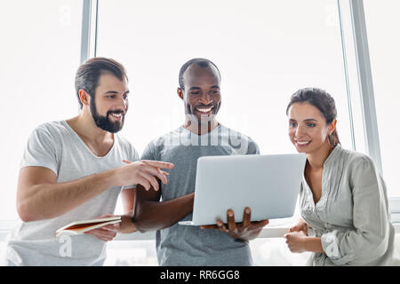 Drei junge Mitarbeiter mit Laptop und diskutieren neue Projekt im Büro, Entwicklung Strategie für On-line-Geschäft, den Austausch von Ideen, die Vorbereitung - Stockfoto