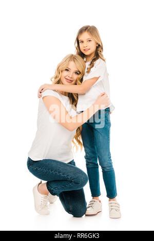 Schöne Frau auf Knie und Umarmen entzückende Tochter isoliert auf weißem - Stockfoto
