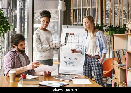 Attraktive junge Frau, die in der Nähe der Tafel mit einem Laptop in der Hand und Suchen zu ihren männlichen Kollegen, die ein Diagramm mit den Ergebnissen. Ein anderer Kollege schaut auf sie mit einem Lächeln. Konzept der Erfolg - Stockfoto