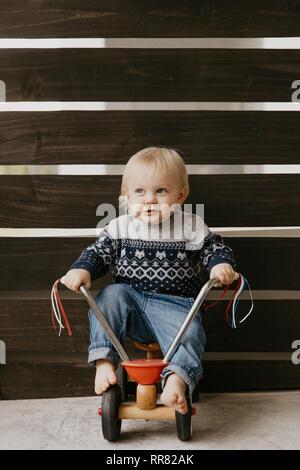 Kostbare adorable kleine süße blonde Baby Kleinkind Junge Spielen draussen auf Holzspielzeug Fahrrad Roller Mobile lächelt in die Kamera und Spaß - Stockfoto