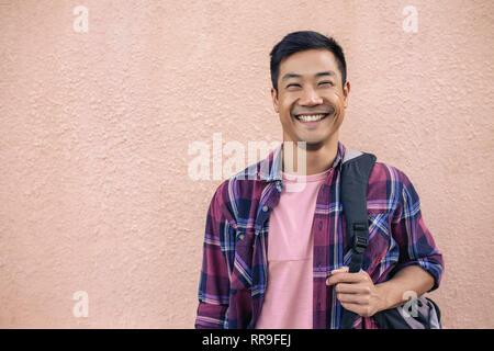 Lächelnden jungen Mann draußen stehen, die einen Rucksack - Stockfoto