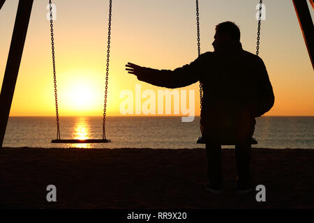 Rückansicht Hintergrundbeleuchtung Silhouette der Mann sitzt auf Schaukel allein fehlt ihr Partner bei Sonnenuntergang am Strand im Winter - Stockfoto