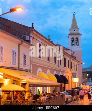 NOVIGRAD, KROATIEN - 20. AUGUST 2017: Leute an einem Street Restaurant bei Dämmerung in Novigrad. Novigrad ist Touristen beliebten Badeort in Croati - Stockfoto