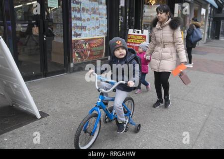 Junge reitet sein Fahrrad mit Stützräder mit Mama und die kleine Schwester hinter gehen auf Kings Highway Bürgersteig in der Midwood Nachbarschaft von Brooklyn, New York. - Stockfoto