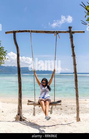Indonesien, Gili Trawangan Insel junge Frau schwingen auf Swing. - Stockfoto