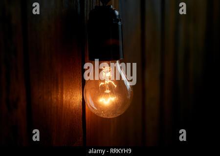 Edison Glühlampe hängt an einem langen Draht. Gemütliche warme gelbe Licht. Retro - Stockfoto
