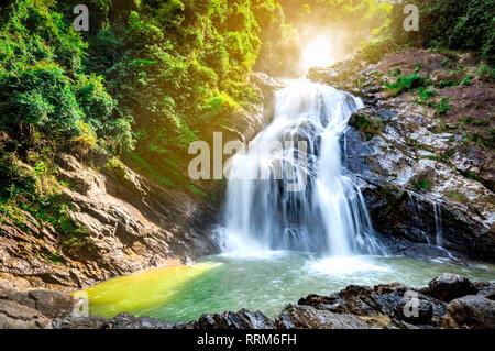 Schönen Wasserfall am Berg mit blauem Himmel und weißen Wolken Cumulus. Wasserfall in tropischen grünen Baum Wald. Wasserfall fließt in den Dschungel. N - Stockfoto