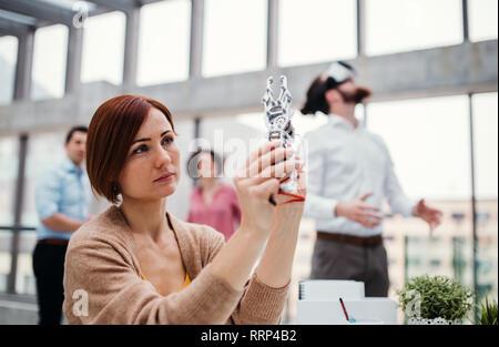 Eine junge geschäftsfrau oder Wissenschaftler mit roboterhand im Büro, arbeiten. - Stockfoto