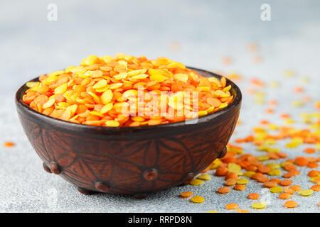 Sortiment trockene bunte Linsen in einem Ton Schüssel close-up. Gelbe und rote Getreide. Vielzahl von Körnungen. Leckeres und gesundes Essen. Selektiver Fokus und - Stockfoto