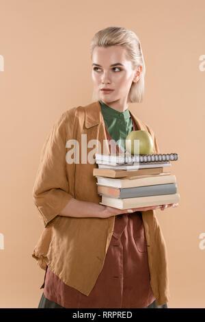 Schöne junge Frau mit Büchern und Green Apple beim Stehen in der eco Kleidung auf beige isoliert - Stockfoto