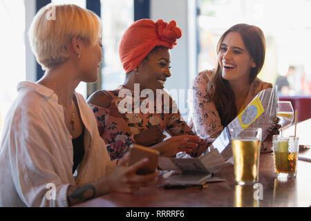 Glückliche junge Frauen Freunde auf Karte, trinken Cocktails in der Bar - Stockfoto