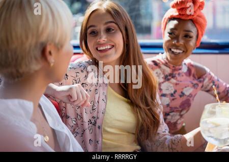 Junge Frauen, die Freunde im Restaurant sprechen - Stockfoto