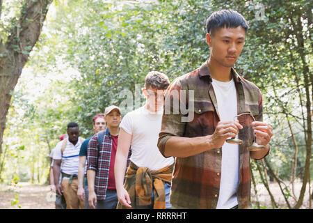Mann mit tingsha Zimbeln führender mens Gruppe Wanderung im Wald - Stockfoto