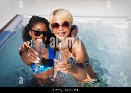 Portrait ausgelassenen jungen Frauen Freunde trinken Champagner im sonnigen Whirlpool - Stockfoto