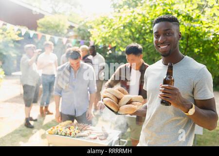 Portrait selbstbewussten jungen Mann trinkt Bier, genießen Barbecue im Sommer Hinterhof - Stockfoto