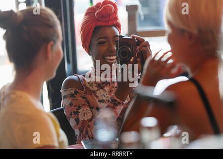 Junge Frau fotografieren Freund mit Digitalkamera im Cafe - Stockfoto
