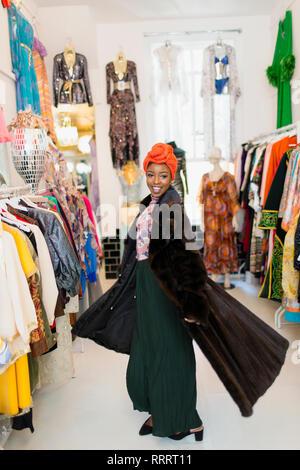 Portrait zuversichtlich, stilvolle junge Frau, die versucht, auf Pelz in Clothing Store - Stockfoto