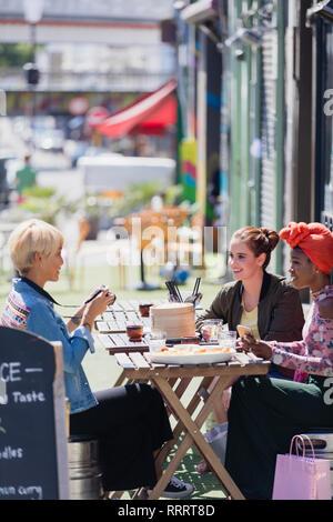 Junge Frauen, die Freunde genießen dim sum Mittagessen im sonnigen Straßencafé - Stockfoto
