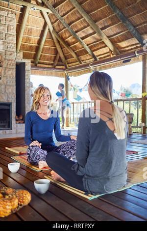 Frauen sprechen und trinken Kaffee in der Hütte während Yoga Retreat - Stockfoto