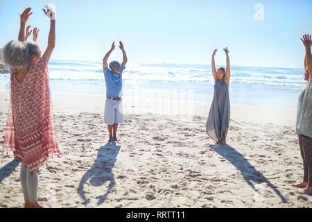Gruppe stehend mit Waffen im Kreis auf sonnigen Strand während Yoga Retreat - Stockfoto