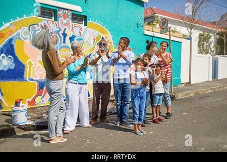 Gerne Freiwillige feiern Wandgemälde an sonnigen Wand - Stockfoto