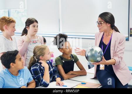 Aufmerksame Schüler beobachten Geographielehrer mit Kugel - Stockfoto