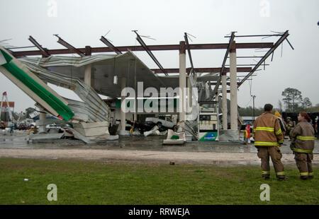 Freiwillige Feuerwehr stehen vor einem zerstörten BP-Tankstelle nach einem EF-2 Tornado in Theodore, Alabama, 9. März 2011. - Stockfoto
