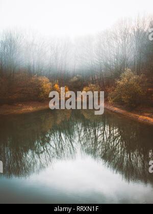 Ruhige See Wasser mit Reflexion der herbstlichen dunkle Bäume im dichten Nebel