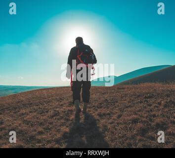 Wanderer auf einem Hügel zu Fuß in Richtung der Sonne - Stockfoto