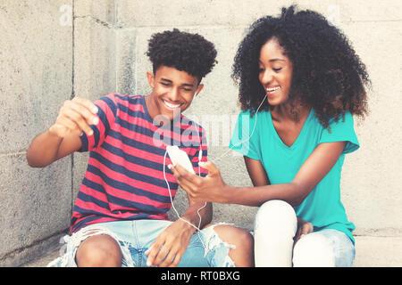 African American junger Erwachsener Paar liebt Musik im Freien im Vintage Retro Look. - Stockfoto