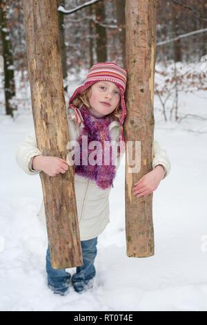 Ein starkes Mädchen, dass einen Baumstamm. Winterliche Landschaft im Wald. - Stockfoto