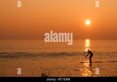 Birling Gap, Eastbourne, East Sussex, UK..27. Februar 2019..Approaching Sunset After Another Glorious Spring Like Day an der Südküste. Paddlebarder auf dem ruhigen Meer, während Nebel sich bewegt, um die Szene zu erweichen. . - Stockfoto