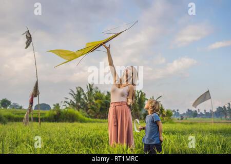 Mutter und Sohn einen Drachen in einem Reisfeld in Ubud, Bali, Indonesien - Stockfoto