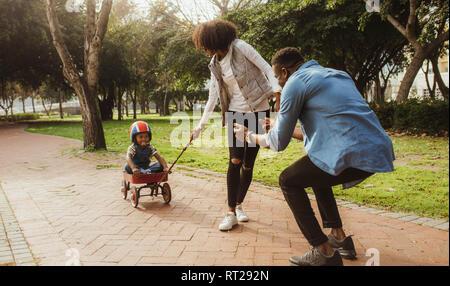 Junge sitzt in einem kleinen Wagen von seiner Mutter gezogen, während Vater stehen mit ausgestreckten Armen. Junge Familie auf dem Genießen im Park. - Stockfoto