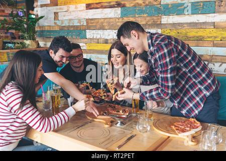 Gerne Freunde teilen Pizza im Restaurant - Freundschaft Konzept mit jungen Menschen Zeit verbringen, zusammen und in echter Spaß im rustikalen Pizzeria eati - Stockfoto