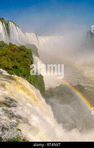 Teufelsschlund Wasserfall in Iguazu Falls mit einem Regenbogen im Vordergrund. - Stockfoto