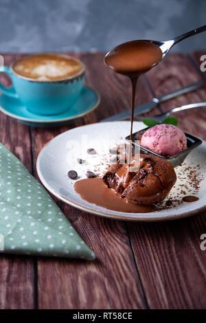 Schokolade Kuchen geschmolzener Lava mit Eis auf dem Teller und Cappuccino. Kugeln Eis im Becher. Dunklen schwarzen Hintergrund - Stockfoto