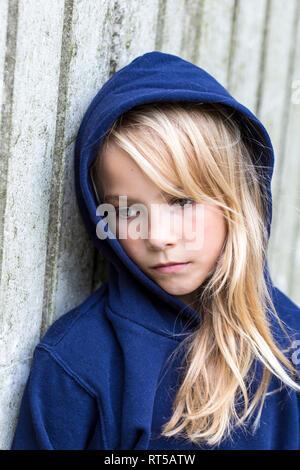 Portrait von traurigen blonde Mädchen trägt blaue Kapuzenjacke gegen Holz Wand lehnt - Stockfoto