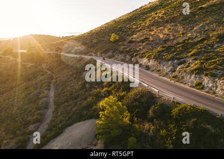Italien, Insel Elba, Biker auf der Küstenstraße gegen die Sonne, Luftaufnahme mit Drone - Stockfoto