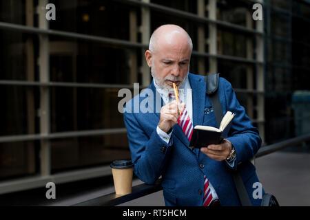 Senior Geschäftsmann Kontrolle Tagebuch im Freien - Stockfoto