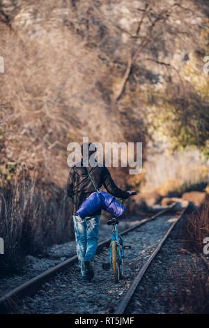 Junge Wandern auf der Bahn mit Fahrrad - Stockfoto