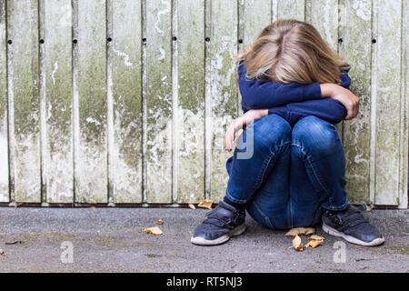 Trauriges Mädchen Hocken vor der hölzernen Wand verbergen ihr Gesicht - Stockfoto