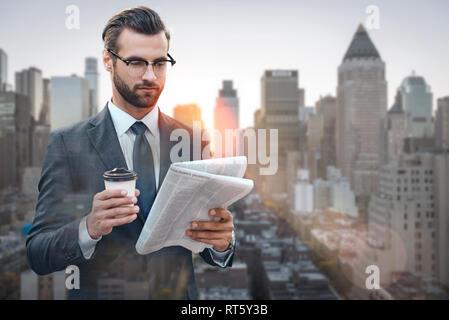Neueste Nachrichten. Reichen und erfolgreichen Geschäftsmann lesen populäre Zeitung und Halten einer Tasse Kaffee im Stehen im Freien mit Skyline im Hintergrund. Informationen. Business Konzept - Stockfoto