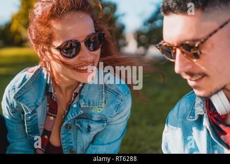 Glückliches junges Paar in Liebe reden, während in einem grünen Park sitzen - Stockfoto