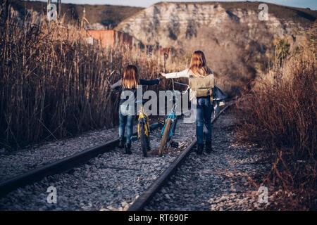 Zwei Mädchen zu Fuß auf der Bahn mit Fahrrädern Stockfoto