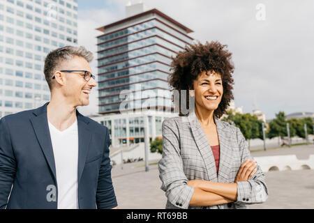 Zwei glückliche Kollegen sprechen außerhalb der Gebäude - Stockfoto