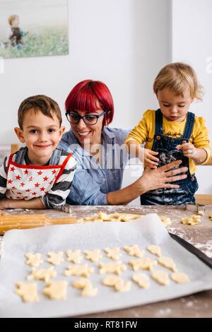 Mutter mit ihren Kindern Kekse backen - Stockfoto